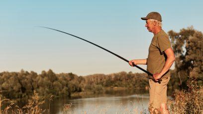 mand i nærheden af en sø fisker